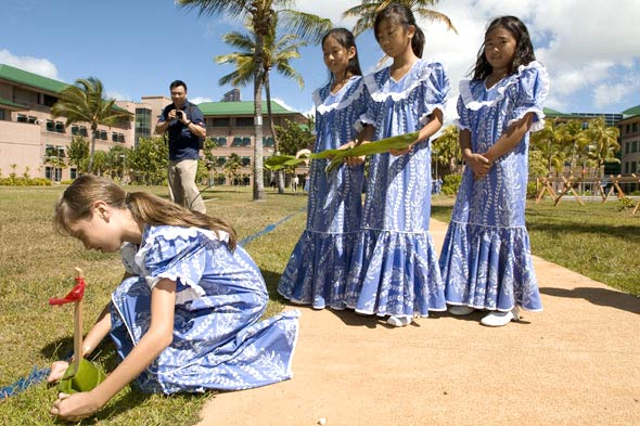 Girls tying leaf to stake