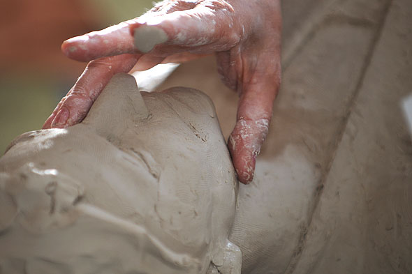 close up of a face being sculpted in clay
