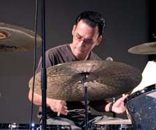 Noel Okimoto on drums