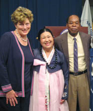 Linda Fujikawa at awards ceremony between fellow volunteer and U.S. diplomat Kathleen Stevens and Chancellor Leon Richards