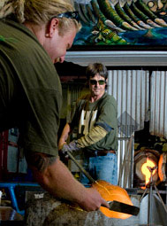 Instructor Rick Mills, at right, works with student Mark Nowicki in the university's glass studio