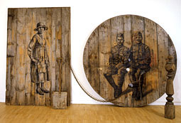 Dawn to Dawn by Whitfield Lovell, 2006, charcoal on wooden barn door and industrial spool disk, chain, newel post, wooden shovel, earth, 97 x 225 inches