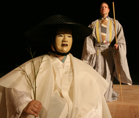 Noriko Katayama in noh mask as a mother searching for her lost child and Jeremy Dowd as a ferryman in <em>Sumida River</em>. Kennedy Theatre photo by Karis Lo
