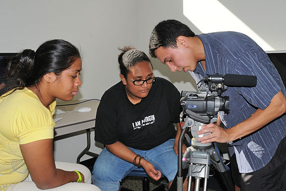 Olelo Community Television's Dane Neves instructs Lusila Mireko and Caroline Halaifonun in the center's editing room