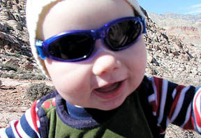 smiling baby wearing sunglasses outdoors
