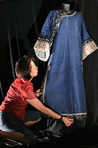 Shu Hwa Lin prepares a Qing Dynasty (1875-1911) lined outer long gown of dark blue damask with floral embroidery cuffs for photography by Karis Lo