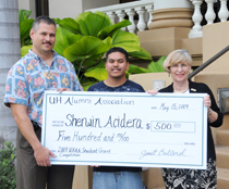 Three people with giant check