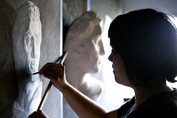 woman working on a drawing of a bust reproduction