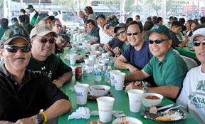 group of men at table tailgating for UNLV-Hawaii football
