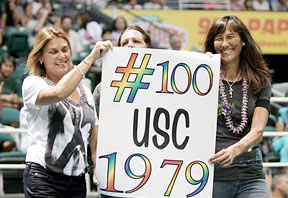three women hold a sign for the 100th win.