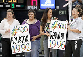 Four women hold two signs for the 500th and 600th win