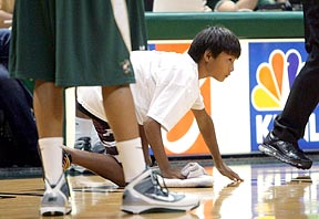a ball boy at the ready during a basketball game