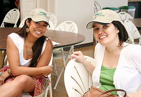 Two women in UH baseball hats