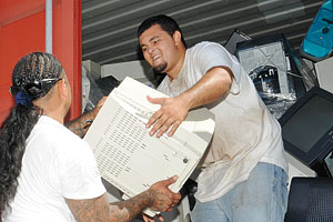 man handing off a giant old computer monitor to another man