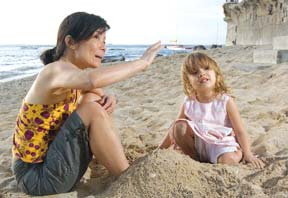 woman and child sitting on beach talking