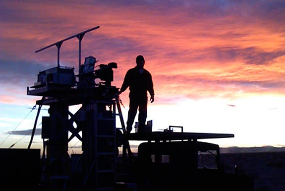 silhouette of scientist standing on equipment and looking at a sunset