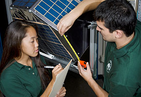 students work on a satellite