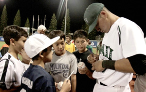 Rainbow Warrior baseball player signing balls for young fans