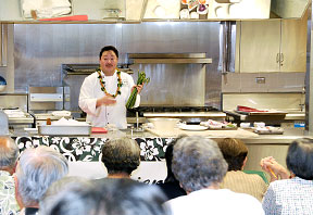 chef in a demonstration kitchen with audience