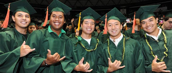 Manoa graduates in cap and gown flashing shaka sign and smiling