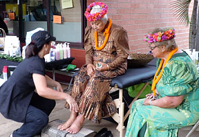 two lovely kupuna in lei getting a massage demonstration