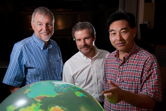 three men in front of a large globe