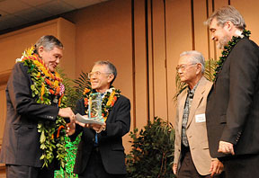 Michael Chun, wearing multiple lei, receiving award from three other men