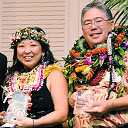 Diane Kodama and Derek Mukai wearing lei and holding awards