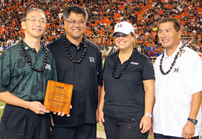 Four people holding plaque on field at football stadium