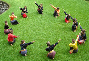 group of people in circle in costume practicing Randai choreography on lawn