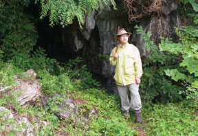 Christopher Bae in hat and holding hammer in front of mountain cave