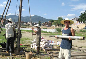 Three men in straw hats working with coring rig