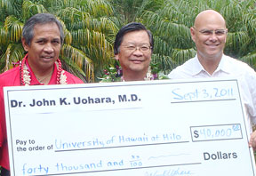 three men holding giant check