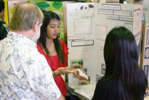 students talking to judge at display board
