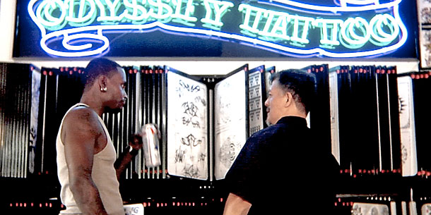 two men standing by tattoo sign