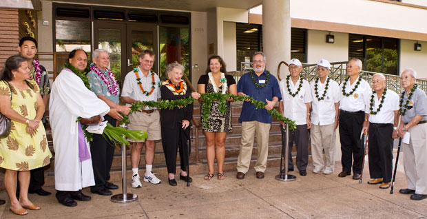 line of people holding maile lei at door to building