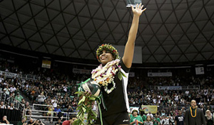 Woman volleyball player with lei on head and around neck waving to crowd in arena