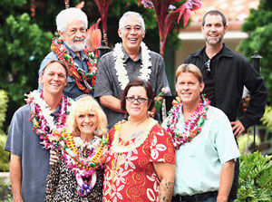 seven artists standing outside wearing lei