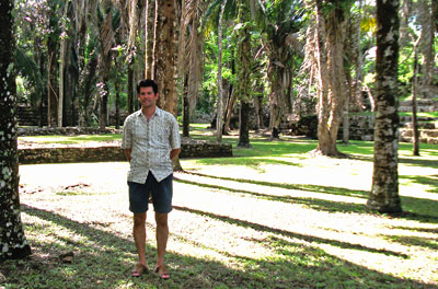 Man in shorts standing amid palm trees