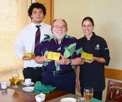 Governor Neil Abercrombie with young man in whie shirt and tie and woman in chef's shirt holding packages