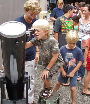child looking through telescope