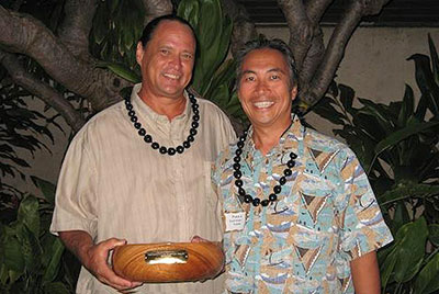 2 men holding koa bowl award