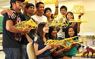 Group of students holding bridges made from spaghetti
