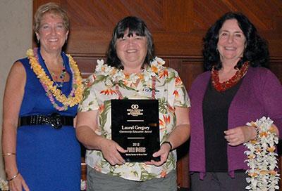 A group of three women at awards presentation