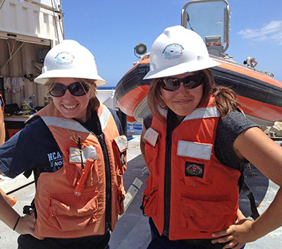 Two women in hard hats and life vests on board a ship