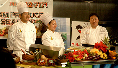 Three people in chef uniform on set of cooking show