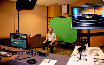 A man sitting in front of a green screen on a television production set.