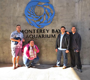 4 people standing by Monterey Bay Aquarium sign