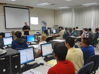 large classroom with a speaker addressing people sitting at computers