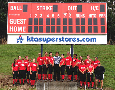 KTA Super Stores President Toby Taniguchi, center, and the 2014 UH Hilo Women's Softball Team standing by the new scoreboard.